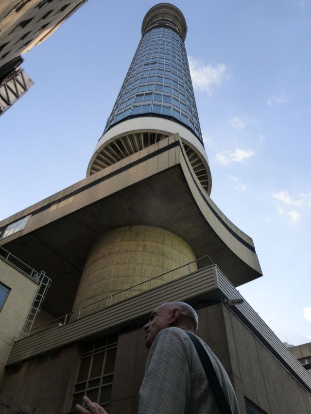 Man standing below BT Tower.