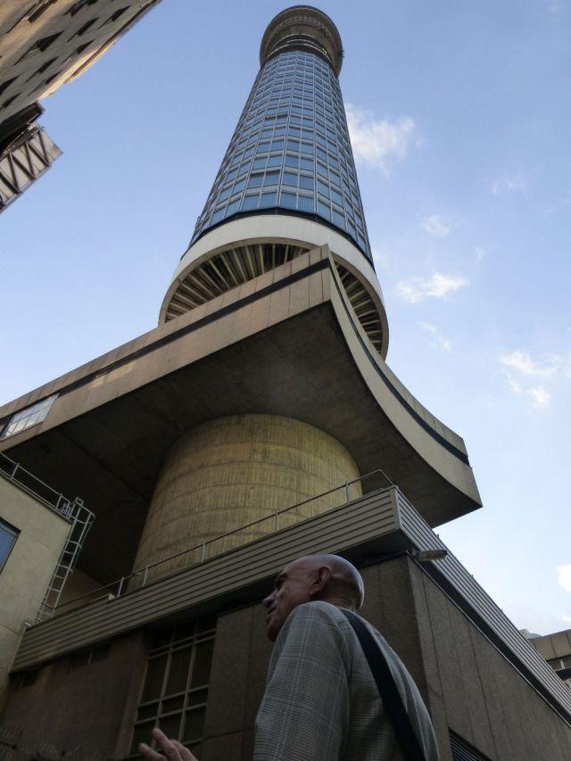 Man standing below BT Tower.